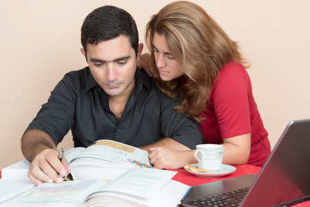 Adult education - Hispanic man and woman studying at home photo