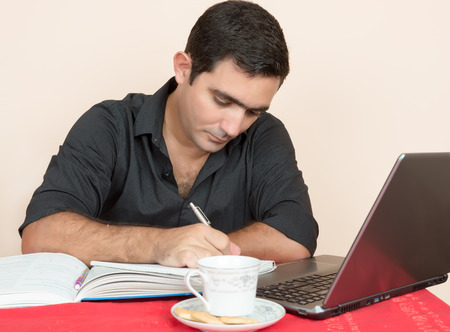Adult education - Hispanic man studying or doing office work at home Stock Photo