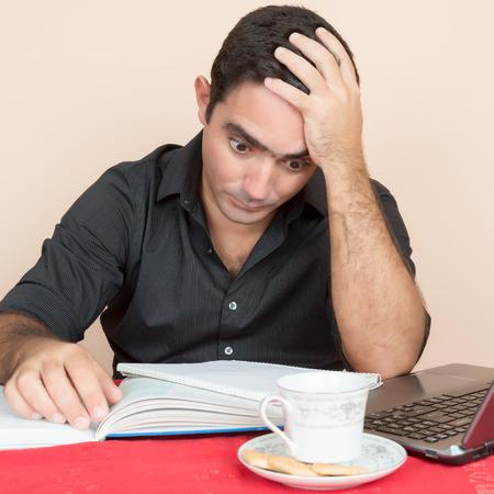 postgraduate: Adult education - Tired hispanic man studying at home