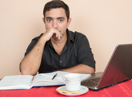 postgraduate: Adult education - Hispanic man studying or doing office work at home