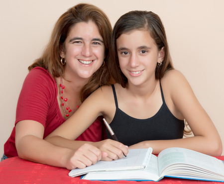 project team: Hispanic teenage girl studying with her mother at home