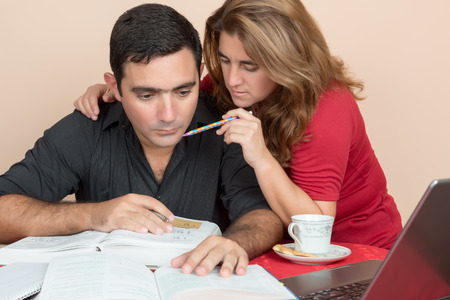 Adult education - Hispanic man and woman studying or doing office work at home photo