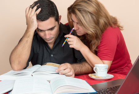 postgraduate: Adult education - Hispanic man and woman studying or doing office work at home