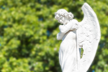angel cemetery: Beautiful angel with an out of focus green trees background Stock Photo