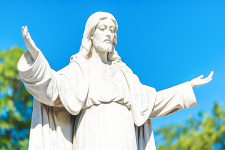 christianism: Statue of Jesus Christ opening his arms  with a clear blue sky background