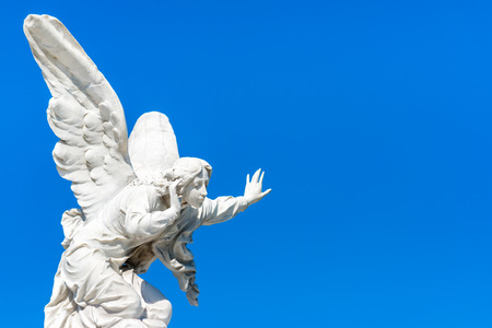 Beautiful angel with a clear blue sky background with space for text Фото со стока