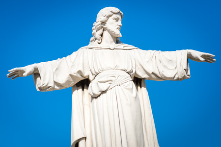 christianism: Statue of Jesus Christ with his arms extended on a clear blue sky background