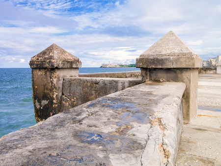 The famous Malecon seawall in Havana with El Morro castle on the background photo