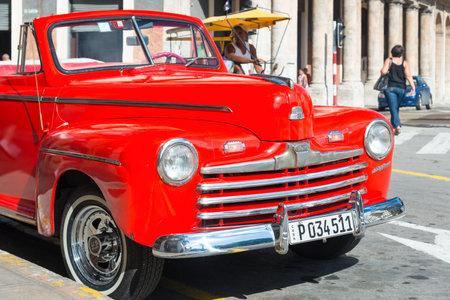 shiny car: HAVANA,CUBA - NOVEMBER 6,2014 : Beautiful and shiny vintage red Ford car parked next to a hotel