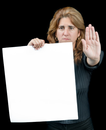 Serious woman gesturing to stop and holding a white banner with space for text isolated on a black background photo