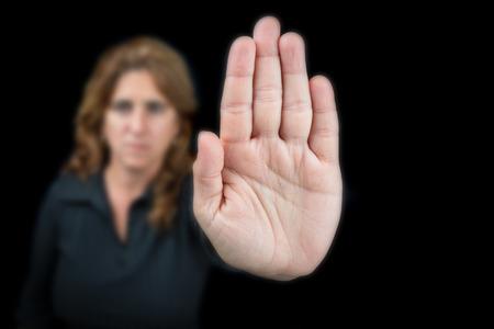 Mujer seria que gesticula para parar aislado en un fondo negro (se centró en la mano)