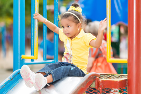 playground ride: Cute small mixed race girl using a slide at a colorful playground