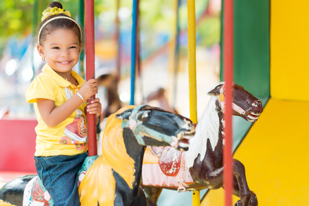 merry go round: Cute small mixed race girl riding a colorful carousel