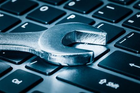 klawiatury: Konserwacja komputera - Metalowe klucz ponad klawiaturze komputera w stonowanych niebieski