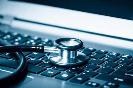 auditoría: PC o análisis de datos - estetoscopio sobre un teclado de computadora portátil en tonos azul