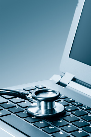 health industry: Computer or data analysis - Stethoscope over a laptop computer keyboard toned in blue