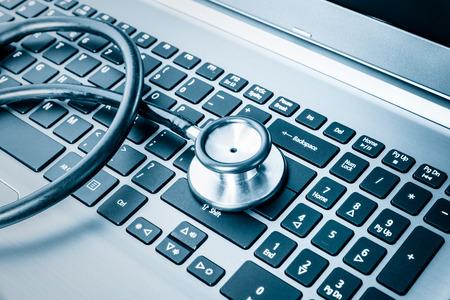 Gezondheid computersysteem of auditing - Stethoscoop over een toetsenbord van de computer in blauw wordt gestemd