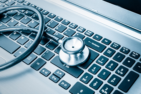 estetoscopio: La salud del sistema del ordenador o auditor�a - estetoscopio en un teclado de computadora en tonos azul