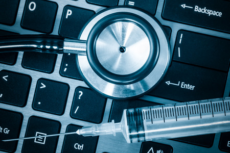 troubleshoot: Computer system health - Stethoscope and syringe on a computer keyboard