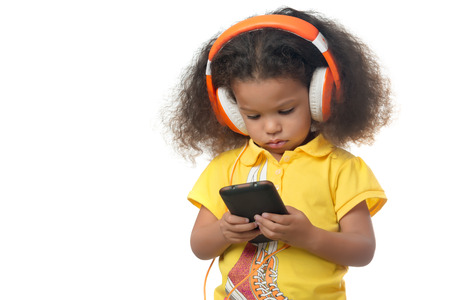 Cute african american small girl listening to music on a cellphone using big orange headphones isolated on white Banque d'images