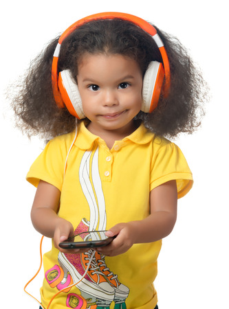 Cute african american small girl listening to music on a cellphone using big orange headphones isolated on white Stock Photo