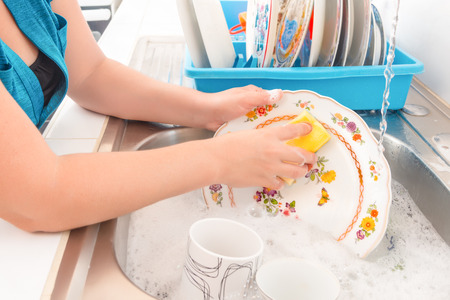 Tareas de la casa - Lavar los platos en el fregadero de la cocina Foto de archivo - 35634217