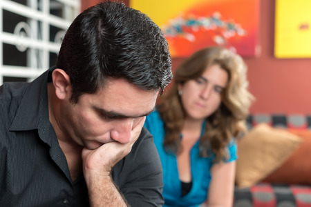 upset man: Divorce, marital problems- Sad and worried man with his wife looking at him