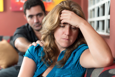 Divorce, marital problems - Sad wife with her husband in the background Stock Photo