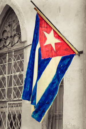 Cuban flag on a grunge decaying neighborhood in Havana photo