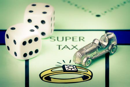monopolio: Símbolo del coche y los dados al lado del espacio IMPUESTO ESTUPENDO en un tablero de juego Monopoly