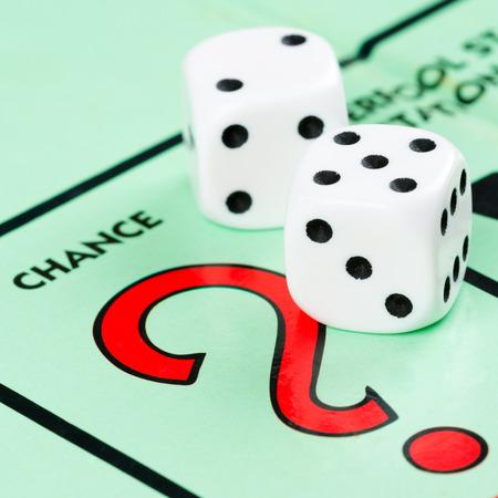 monopolio: Par de dados al lado del espacio de dibujo carta de juego en un tablero de juego Monopoly