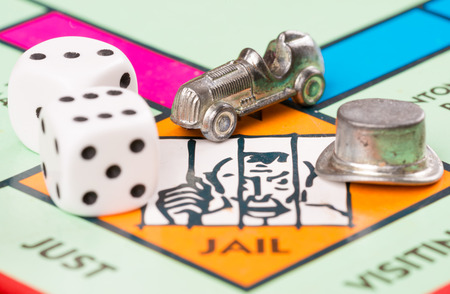 token: LONDON,UK - FEBRUARY 11, 2015 : Dice and car token next to the JAIL space in a Monopoly game board Editorial
