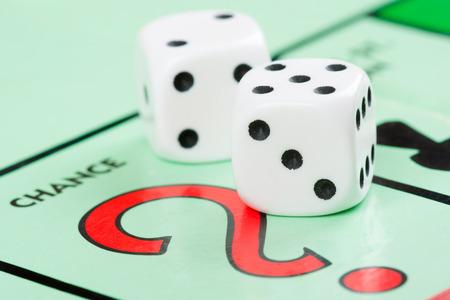 monopolio: Par de dados al lado del espacio de dibujo carta de juego en un tablero de juego Foto de archivo