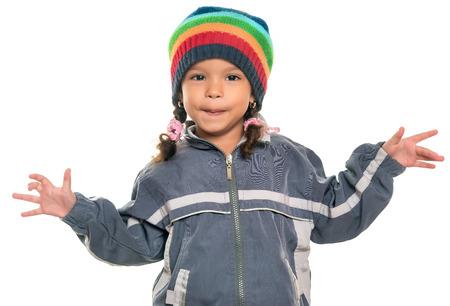 Mestiza niña con una actitud divertida que lleva un colorido gorro y una chaqueta aislados en blanco