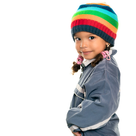 Funny mixed race small girl wearing winter clothes and a colorful beanie hat isolated on white