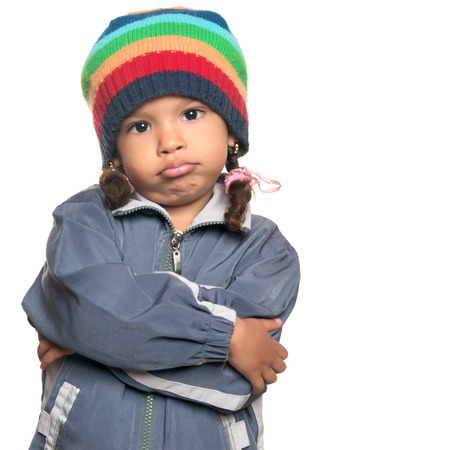 disobedient child: Funny mixed race little girl wearing a colorful beanie hat and a jacket with a rapper attitude isolated on white