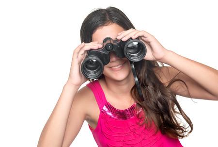 Beautiful teenage girl looking through a pair of binoculars isolated on white photo