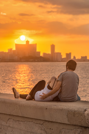 Romantic young couple looking at a beautiful sunset over the city of Havana Stock Photo