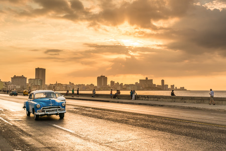 classic car: The sun setting over the city of Havana with a view of the Malecon avenue
