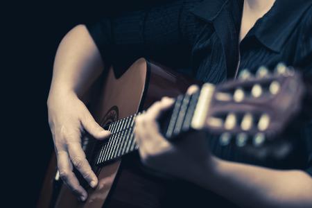 orquesta clasica: Guitarra cl�sica - Vintage imagen de tonos de las manos del m�sico tocando una guitarra ac�stica Foto de archivo