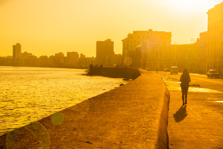 seawall: Backlit image of a colorful sunrise in Havana with a view of the malecon seawall and the city skyline Stock Photo