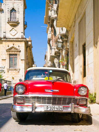 chevrolet: Vintage red car on a narrow street on the colonial neighborhood of Havana