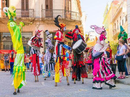 Colorful stiltwalkers tanzen zu den Klängen der kubanischen Musik in Alt-Havanna Standard-Bild - 39011427