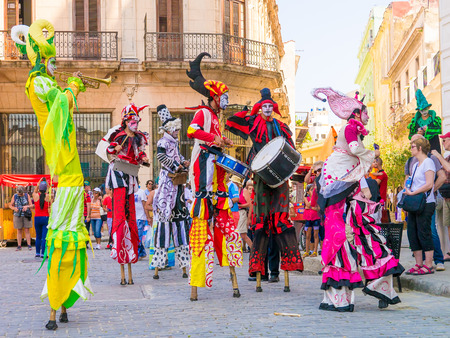 Colorful stiltwalkers dancing to the sound of cuban music in Old Havana