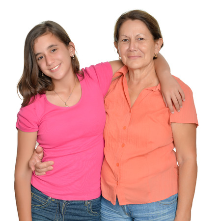 puberty: Hispanic teenage girl and her grandmother hugging and smiling isolated on white Stock Photo
