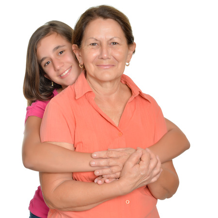 Hispanic teenage girl and her grandmother hugging and smiling isolated on white Фото со стока