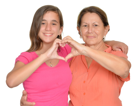 love and friendship: Hispanic teenage girl and her grandmother hugging and doing a heart sign with their hands
