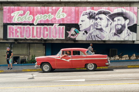 propaganda: Vintage american car next to a poster supporting the Cuban Revolution Stock Photo