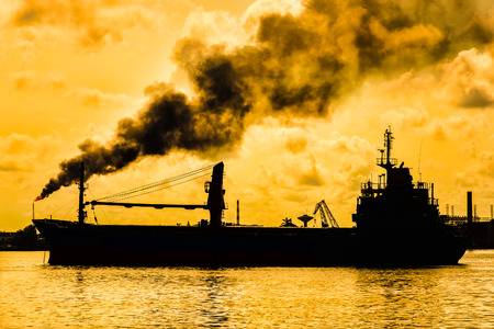 sea pollution: Oil refinery releasing a huge smoke column polluting the air with the silhouette of a ship on the foreground