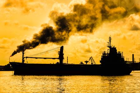 camión cisterna: Refinería de petróleo liberando una enorme columna de humo que contamina el aire con la silueta de un barco en el primer plano